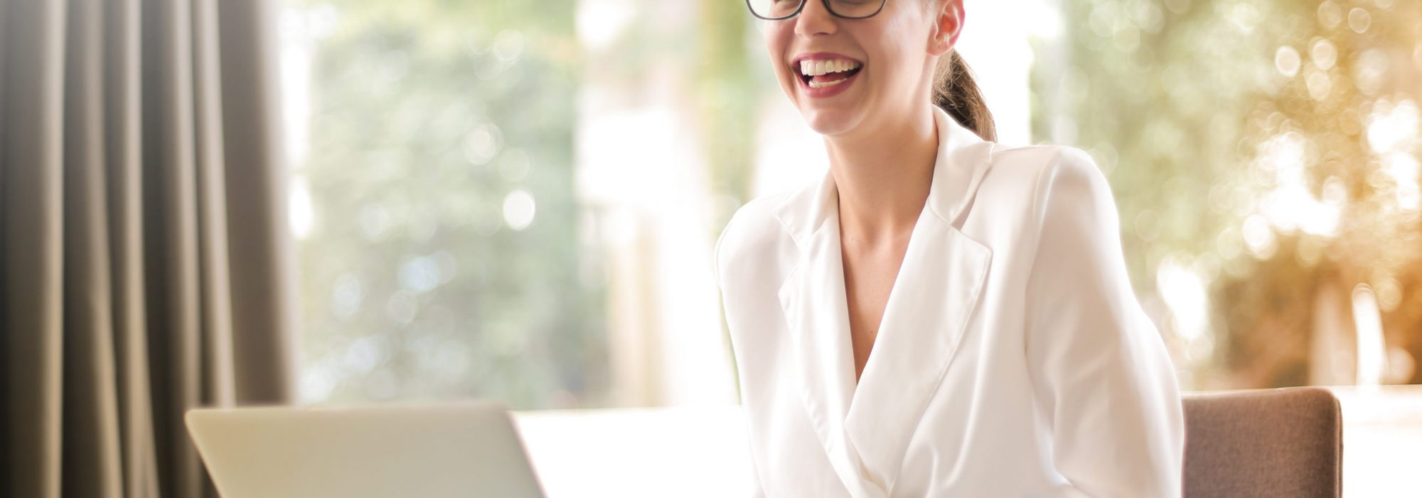 laughing-businesswoman-working-in-office-with-laptop-3756679